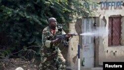 Un soldat armé d'un AK-47 tire sur les manifestants opposés à un trosième mandat du président Pierre Nkurunziza à Bujumbura, Burundi, lundi 25 mai 2015