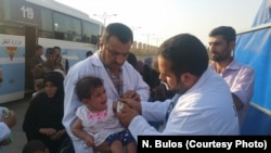 Medics at this collection point for fleeing families treat a baby for malnutrition, which they say is widespread among children in Mosul, Iraq, on July 12, 2017.