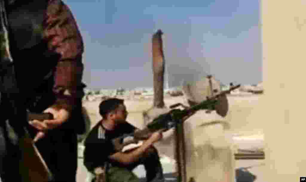 This image made from amateur video released by the Ugarit News shows a Free Syrian Army solider firing his weapon during clashes with Syrian government troops in Aleppo, Syria, July 24, 2012.