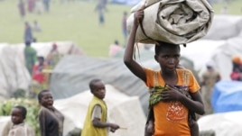 A newly arrived refugee from the Democratic Republic of Congo carries her belongings at a makeshift refugee camp at Bunagana near Kisoro town in Uganda, May 15, 2012.