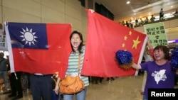 亲中国的台湾活动人士在桃园机场手举中国和台湾旗帜欢迎大陆海协会会长张志军访问台湾。(2014年6月25日)