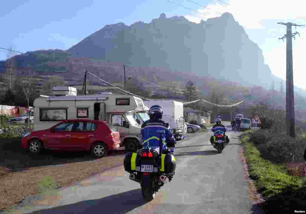 French Gendarmes patrol a street where mobile-homes are parked, on December 20, 2012, in the French southwestern village of Bugarach.