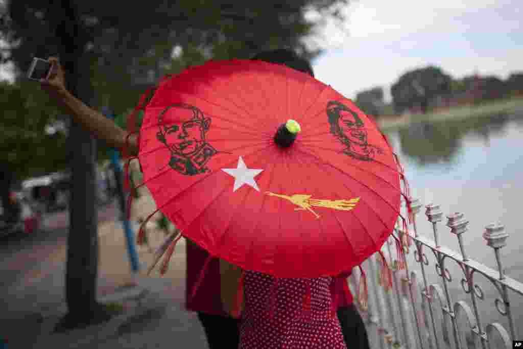 A group of people with an umbrella displaying pictures of Myanmar's opposition leader Aung San Suu Kyi, her late father General Aung San, and the logo of Suu Kyi's National League for Democracy party take pictures of themselves in Mandalay. Myanmar's general elections are scheduled for Nov. 8, 2015, the first since a nominally civilian government was installed in 2011.