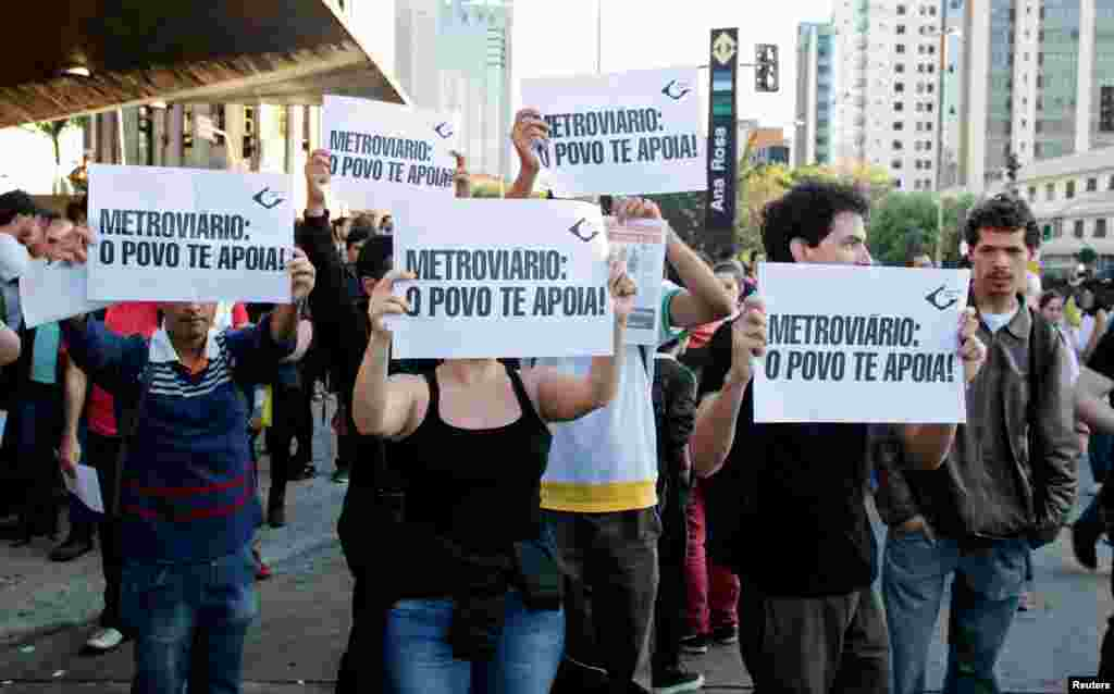 """Residents hold up signs that read, """"Metro workers: The people support you,"""" outside Ana Rosa subway station during the fifth day of metro workers' strike in Sao Paulo, Brazil, June 9, 2014."""