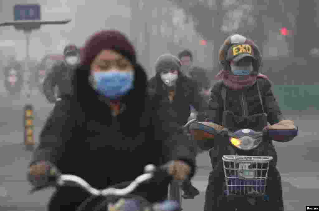 Pessoas usam máscara de protecção enquanto andam de bicicleta, num dia de nível extremo de poluição em Pequim. China, 8 de Dezembro 2015