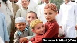 عید کے موقع پر گلے ملتے اور ایک دوسرے کو مبارکباد دیتے بچے