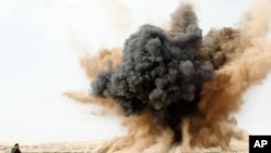 A rebel holds his ears as a bomb launched by a Libyan air force jet loyal to Libya's leader Muammar Gaddafi explodes in the desert near Brega, March 2, 2011