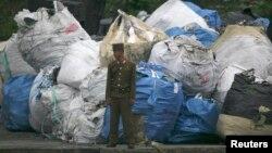 북한 신의주 압록강 유역에서 북한 군인이 쓰레기 더미 앞에 서 있다. (자료사진)