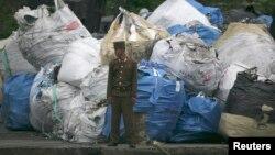 Một binh sĩ Bắc Triều Tiên đứng canh gác trước một đống rác trên bờ sông Yalu, gần thị trấn Sinuiju ở Bắc Triều Tiên đối diện với thành phố Đan Đông của Trung Quốc.