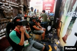 "FILE - Attendees wearing Oculus Rift virtual reality headsets view a 3-dimensional video for the ""Pacific Rim: Jaeger Pilot"" video game during the 2014 Comic-Con International Convention in San Diego, California, July 25, 2014."