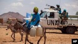Seorang mengendarai keledai di Khor Abeche, Darfur, Sudan, sementara pasukan perdamaian PBB tampak siaga di belakangnya (foto: dok).