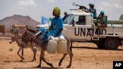 Un homme, monté sur un ane, dépasse un convoi de la mission des Nations unies dans le sud du Darfour, Soudan, le 30 juin 2014