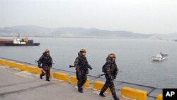 ژمارهیهک سهربازی مارینی کۆریای باشور باسهوانی لهسهر کهنارێـکی دهریای زهرددا دهکهن، سێشهممه 21 ی دوازدهی 2010