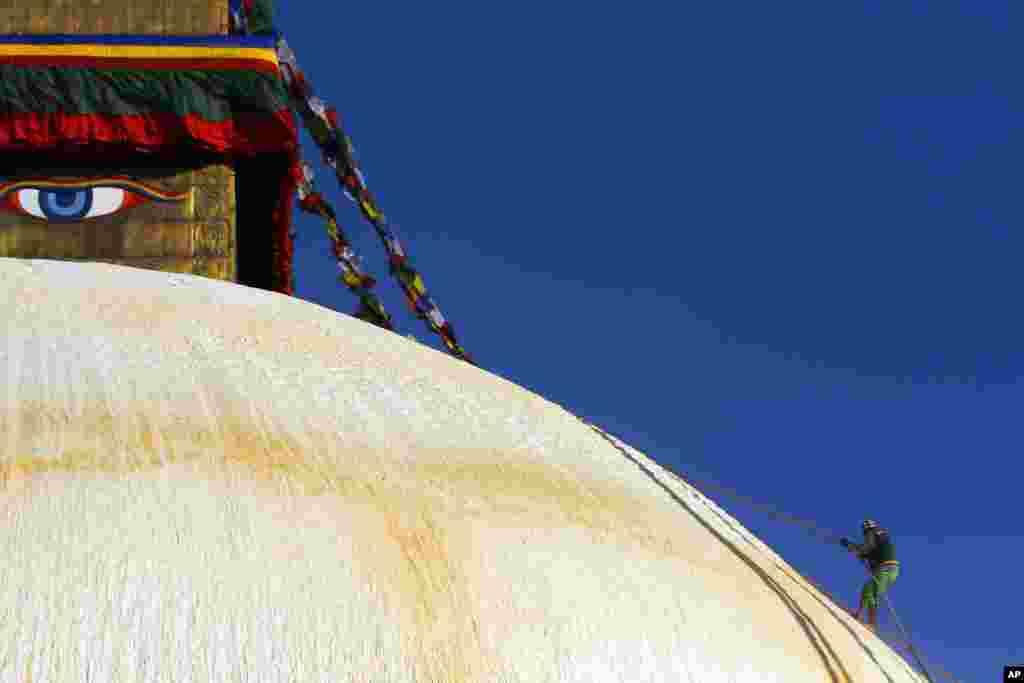A Nepalese man climbs the Boudhanath stupa in Katmandu, a world heritage site, for renovation.