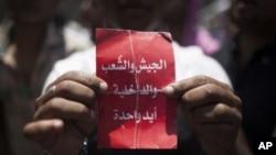 """Tahrir Meydanında"""" ordu, halk, polis elele"""" yazılı kart tutan bir gösterici"""