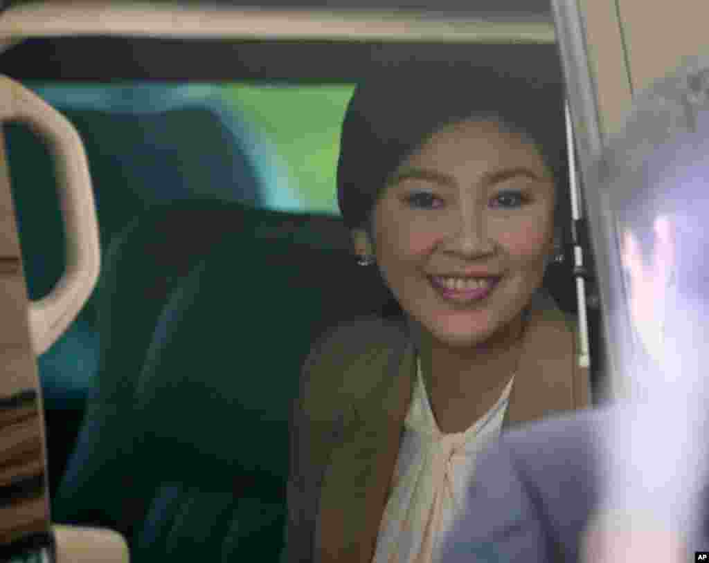 Prime Minister Yingluck Shinawatra sits in a car as she leaves the Thai Air Force headquarters after a cabinet meeting in Bangkok, Feb. 25, 2014.