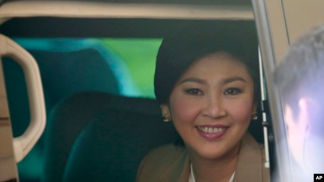 FILE - Prime Minister Yingluck Shinawatra sits in a car as she leaves the Thai Air Force headquarters after a cabinet meeting in Bangkok, Thailand.