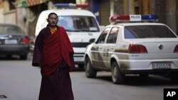 An ethnic Tibetan monk walks past a police station in Danba, Sichuan province. Ethnic tension simmered in remote corners of China's southwestern Sichuan province after security forces fired on demonstrators in a series of deadly clashes that Tibet's gover