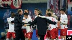 L'entraîneur de Leipzig, Ralph Hasenhuettl, à gauche, jubile avec son équipe après le coup de sifflet final du match de football de la Bundesliga allemande entre le RB Leipzig et le FC Schalke 04 à Leipzig, en Allemagne, 3 décembre 2016.