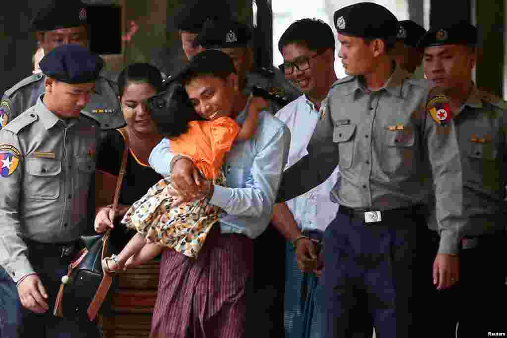 Detained Reuters journalist Kyaw Soe Oo hugs his daughter as he is escorted by police, arrives for a court hearing in Yangon, Myanmar.