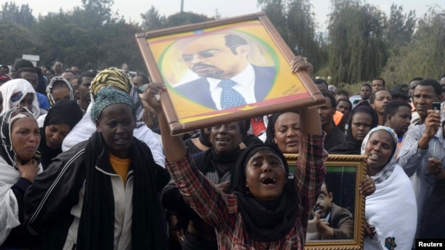 A woman wails while lifting a portrait of the late Ethiopian Prime Minsiter Meles Zenawi as she waits for the arrival of his remains in the capital Addis Ababa, August 21, 2012.