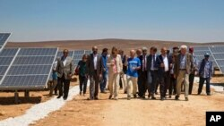 Officials from the IKEA Foundation, and the U.N. refugee agency tour a newly inaugurated solar energy plant, that will provide about 20,000 Syrian refugees with electricity, in the Azraq Refugee Camp, Jordan, Wednesday, April 17, 2017. The foundation funded the plant which makes Azraq, run by the UN, the world's first refugee camp to be powered by renewable energy and saves $1.5 million a year in electricity costs.