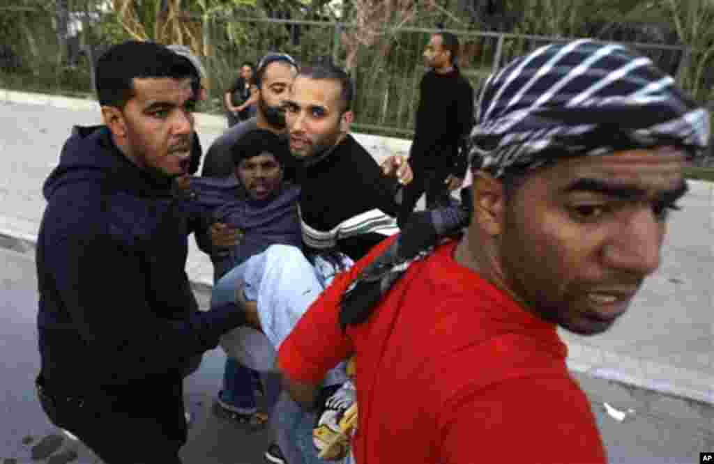 An unidentified Bahraini anti-government protester is carried to a vehicle to be taken to a hospital after being wounded during a demonstration in Manama, February 18, 2011. (AP Image)