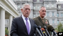 Defense Secretary Jim Mattis, left, accompanied by Joint Chiefs Chairman Gen. Joseph Dunford, right, makes a statement on North Korea to members of the media outside the White House in Washington, Sunday, Sept. 3, 2017