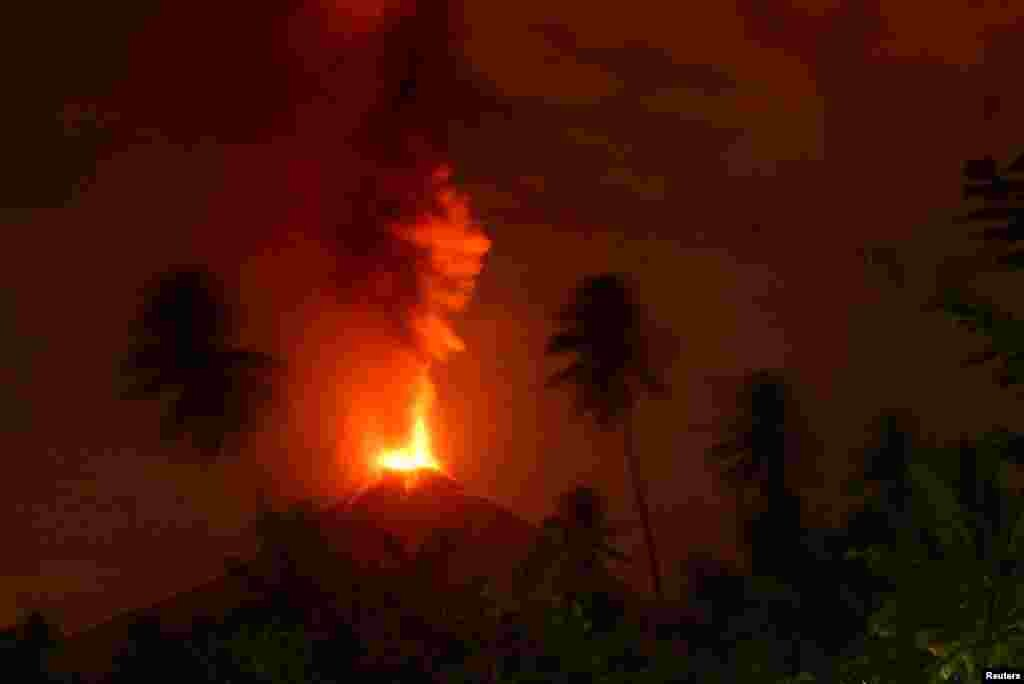 The Mount Soputan volcano bursts October 3, as seen from Lobu village in Southeast Minahasa regency, North Sulawesi, Indonesia.