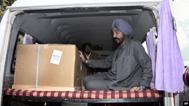 Indian student Nitin Garg's relative Pritam Singh sits in an ambulance besides Garg's body, at the cargo terminal of international airport in New Delhi, India (File Photo)