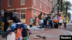 Pengungsi yang mengungsi akibat Badai Laura memeriksa barang-barang yang telah diturunkan di pinggir jalan di luar New Orleans Marriott di New Orleans, Louisiana, AS, 30 Agustus 2020. (Foto: Reuters)