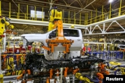 FILE - Robots swing a cab and bed into place for a new heavy duty pickup truck on the assembly line where Chevrolet Silverado trucks are being built at General Motors Flint Assembly in Flint, Michigan, Jan. 30, 2019.