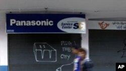 """Hai người dân Miến Điện đi ngang qua hình vẽ với hàng chữ """"Hãy cấp điện thành phố"""". Người ta có thể thấy hàng chữ này nhiều nơi ở Rangoon từ khi chính phủ cắt giảm điện tiêu thụ"""