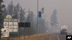 In this photo provided by the U.S. Forest Service a pickup pulls a camper through the wildfire smoke in Seeley Lake in Missoula County, Mont., Aug. 10, 2017. Health officials in western Montana are strongly recommending residents of Seeley Lake leave town because of hazardous smoke from area wildfires.