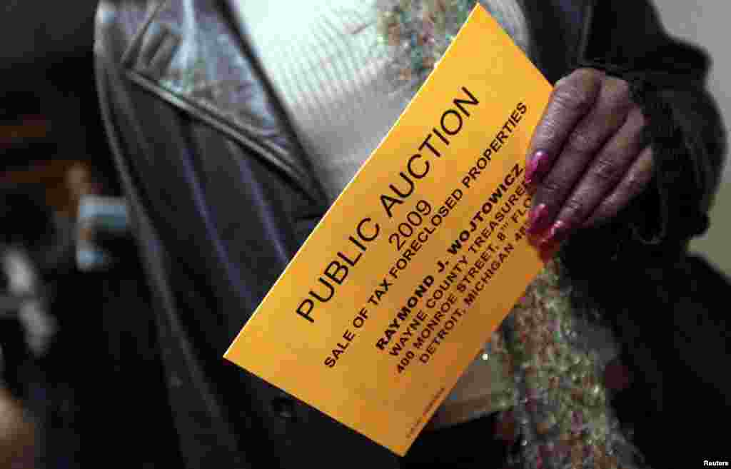 Carla Lyons holds her bidders card as nearly 9,000 foreclosed Detroit area properties are being auctioned off at the International Center Building in Detroit. Picture taken October 19, 2009.