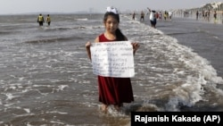 In this Friday, Feb 21, 2020, photo, environmental activist Licypriya Kangujam, 8, holds a sign at Juhu beach during a cleaning drive in Mumbai, India.