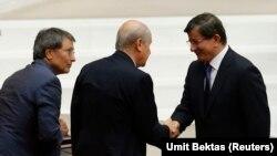Geçen yıl Ağustos ayında Recep Tayyip Erdoğan'ın Cumhurbaşkanlığı töreninde el sıkışan MHP lideri Bahçeli ve yeni Başbakan olan AKP lideri Ahmet Davutoğlu (Arşiv)