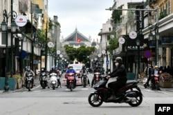 Pengendara motor di sebuah jalan di Hanoi setelah pemerintah Vietnam melonggarkan karantina wilayah untuk mencegah penyebaran virus corona, 23 April 2020.