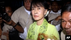 Burmese opposition leader Aung San Suu Kyi, center, arrives at Rangoon International airport to leave for United State Sunday, Sept . 16 2012, in Yangon.