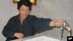 지난 2005년 평양 인근 농장에서 북한 주민이 외부 지원으로 지어진 급수시설을 사용하고 있다. (자료사진)