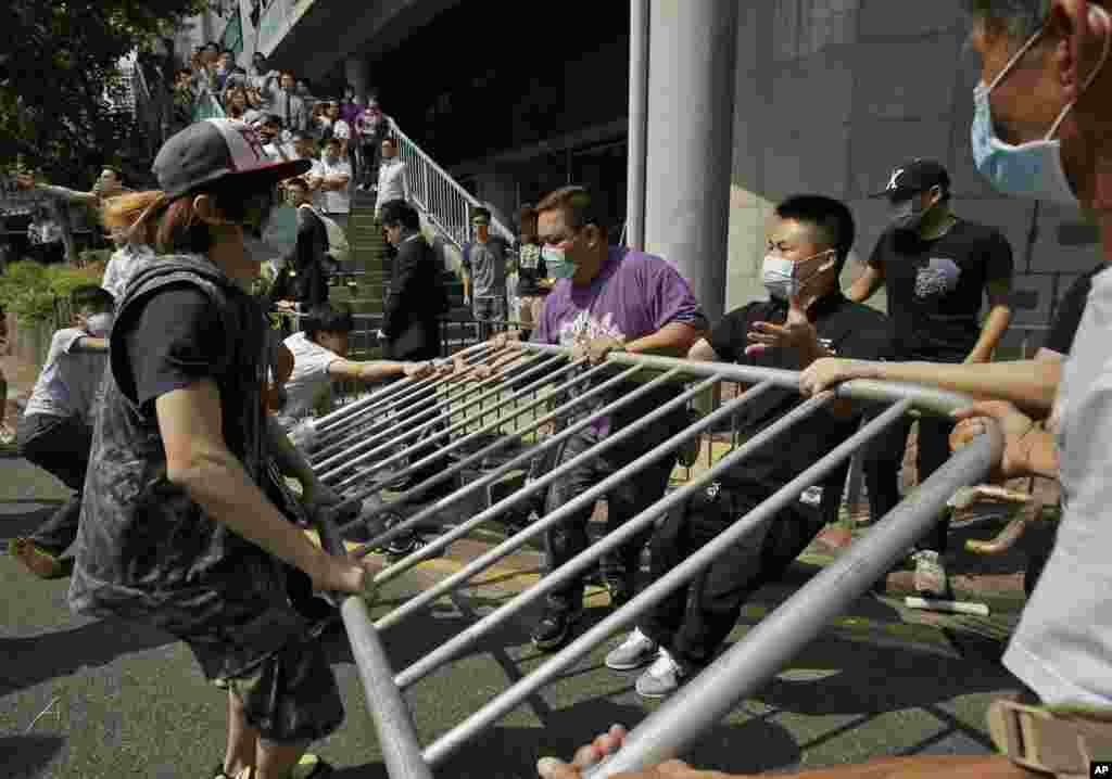 People wearing protective masks remove the metal barricades that protesters set up to block off main roads near the heart of the city's financial district, Hong Kong, Oct. 13, 2014.