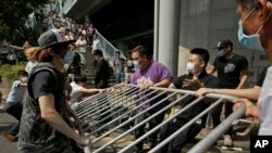 Những người đeo khẩu trang giận dữ tháo dỡ những rào chắn do sinh viên biểu tình dựng lên tại trung tâm Hong Kong, ngày 13/10/2014.