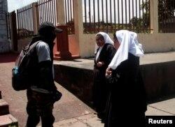 Un partidario del gobierno habla con religiosas frente a una iglesia en Partidarios del gobierno parados frente a una iglesia en Diriamba, Nicaragua, julio 9,2018. REUTERS / Oswaldo Rivas.