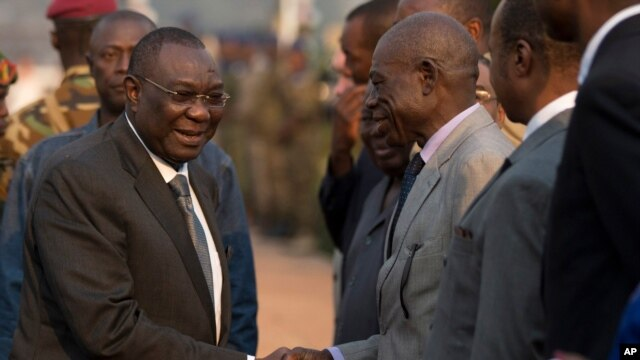 Central African Republic President Michel Djotodia, left, shakes hands with assembled dignitaries as he departs for Chad, at Mpoko Airport in Bangui, CAR, Jan. 8, 2014.