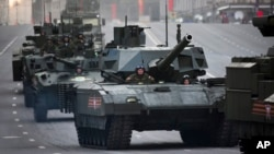 Russian military vehicles including the new Russian T-14 Armata tank, center, make their way to Red Square during a rehearsal for the Victory Day military parade which will take place on May 9 to celebrate 70 years after the victory in WWII, in Moscow, May 4, 2015.