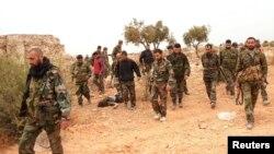 Pasukan setia Presiden Bashar al-Assad membawa senjatanya sambil berpatroli di desa Aziza, Aleppo (25/11).