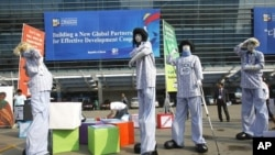 Members from Save the Children and World Vision demonstrate for for effective aid in front of the venue of the fourth High-Level Forum on Aid Effectiveness in Busan, South Korea, November 29, 2011.