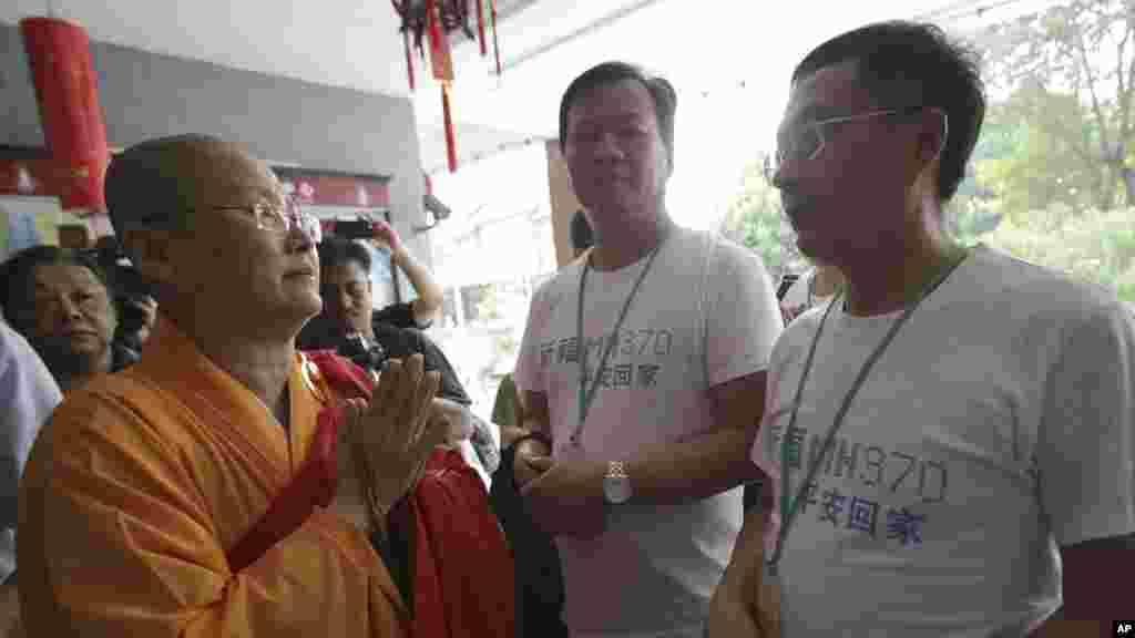 A Buddhist monk welcomes Chinese relatives of passengers on Flight MH370 as they arrive to pray at a Buddhist temple in Petaling Jaya, Malaysia, March 31, 2014.