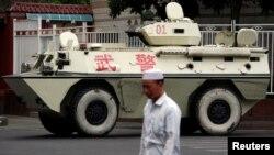 지난 2009년 중국 서부 신장 위구르 자치구 우루무치에서 현지 주민이 중국군의 병력 수송용 장갑차 옆을 지나고 있다. (자료사진)