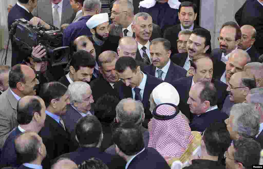 Syria's President Bashar al-Assad (C) chats with people after prayers for Eid al-Adha at al-Afram Mosque, Damascus, Syria, October 26, 2012.